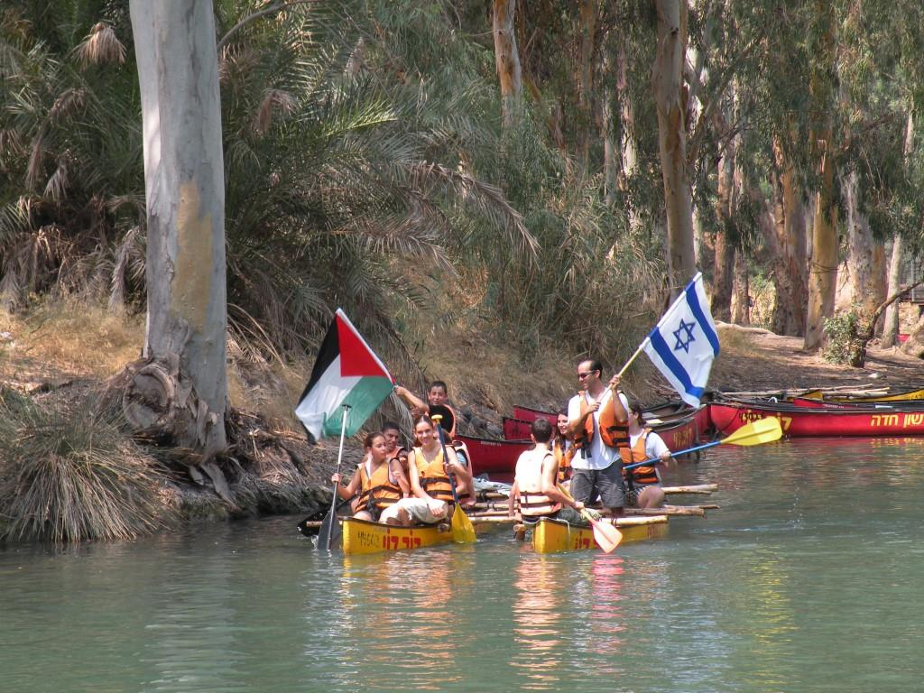 Youth in canoes and flags, Jordan River
